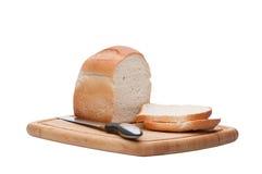 Crusty Loaf of Bread On Breadboard. A Crusty loaf of bread with bread knife laying on breadboard Stock Photo
