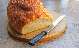 Crusty loaf of bread on wooden board. Stock Photos