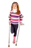 Crutches. Little girl with crutches isolated in white stock image
