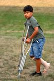 Crutches are Not Fun!. Young elementary boy walking across a lawn on crutches, one foot up and wrapped in an elastic bandage Royalty Free Stock Image