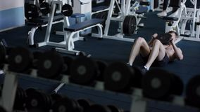 Cruunches jovenes del deportista su ABS con el peso adicional en un gimnasio almacen de video