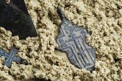 Cruz antiga wearable para vestir imediatamente após o século XVII na areia amarela molhada fotografia de stock royalty free