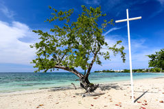 Cruz blanca en una playa con el árbol verde Imágenes de archivo libres de regalías