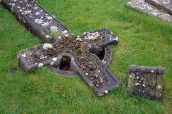 Cruz celta destruída velha na grama no cemitério Foto de Stock