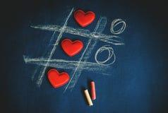 Cruz cero de corazones y de creyones coloreados en fondo oscuro fotos de archivo