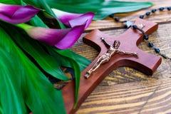 Cruz com jesus christ em um fundo de madeira com um calla roxo - easter religioso emprestou o conceito fotografia de stock