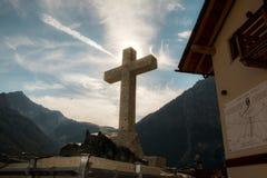 Cruz com sol e montanhas no fundo imagem de stock