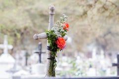 Cruz con algunas rosas Imagen de archivo libre de regalías