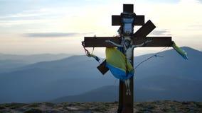 Cruz con la bandera y dios en ella en la puesta del sol - montaña Goverla de Ucrania almacen de video