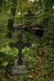 Cruz cristã em arvoredos selvagens da vegetação verde no cemitério velho imagem de stock royalty free