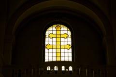 Cruz cristiana amarilla hecha del vidrio en la ventana Símbolos de la fe Crucifixión de Jesús imagen de archivo libre de regalías