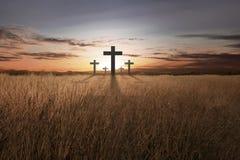 Cruz cristiana brillante en la puesta del sol Fotografía de archivo