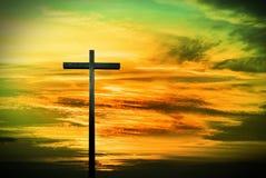 Cruz cristiana en fondo verde y amarillo de la puesta del sol Imagen de archivo