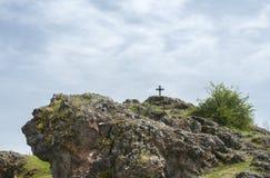 Cruz cristiana en la colina rocosa Fotografía de archivo libre de regalías