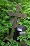 Cruz cristiana en matorrales salvajes de la vegetación verde en el cementerio viejo Foto de archivo libre de regalías