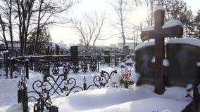 Cruz cristiana en sepulcro en cementerio o cementerio en invierno en bosque almacen de metraje de vídeo