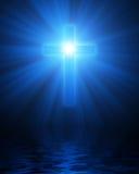 Cruz cristiana que brilla intensamente azul Fotografía de archivo