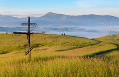 Cruz-crucifijo en el prado en la salida del sol en el fondo del mou Foto de archivo libre de regalías