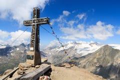 Cruz da cimeira e bandeira da oração na montanha Kreuzspitze com panorama da geleira e Grossvenediger, cumes de Hohe Tauern, Áust Imagens de Stock Royalty Free