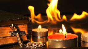 Cruz da cristandade e velas e fogo atrás video estoque
