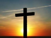 Cruz de Jesús en la puesta del sol imagenes de archivo