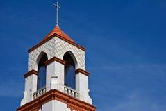 Cruz de la aguja de la iglesia y cielo azul Fotos de archivo