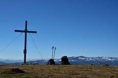 Cruz de la cumbre con las mochilas al lado de ella Fotografía de archivo