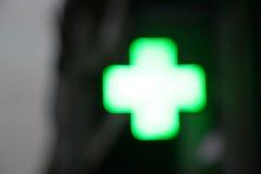 Cruz de la luz de una farmacia, borrosa Imagen de archivo