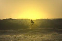 Cruz de la persona que practica surf de la puesta del sol una onda Fotos de archivo