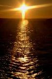 Cruz de la puesta del sol Foto de archivo libre de regalías