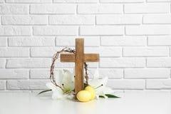 Cruz de madeira, coroa de espinhos, ovos da páscoa e lírios da flor na tabela imagem de stock