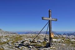 Cruz de madeira em uma parte superior da montanha com pedras e cumes de Berchtesgadens da grama Fotografia de Stock