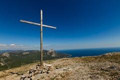 Cruz de madera cristiana en el top de la montaña, la cumbre rocosa, el paisaje inspirado hermoso con el océano, las nubes y el ci Foto de archivo