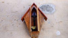 Cruz de madera en la pared de ladrillo de piedra en caja imagenes de archivo