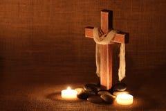 Cruz de madera por luz de una vela y piedras con el fondo lamentable fotografía de archivo libre de regalías