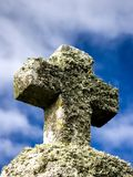 Cruz de pedra com as plantas com o céu como o fundo imagens de stock