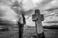 Cruz de pedra cristã antiga e silhueta borrada do homem imagem de stock royalty free