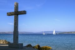 Cruz de pedra instalada perto do mar Simbolismo cristão No fundo é o mar fotografia de stock