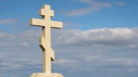 Cruz de pedra ortodoxo contra o fundo do céu azul, opinião no deus, religião filme