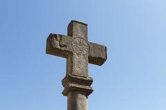 Cruz de piedra antigua con la marca solar y el cielo azul Fotos de archivo