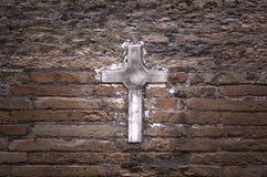 Cruz de piedra en fondo de la pared Imagen de archivo