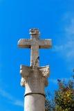 Cruz de piedra en una columna Foto de archivo