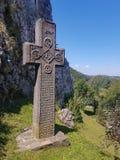 Cruz de piedra medieval con símbolos religiosos imágenes de archivo libres de regalías