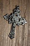 Cruz de plata en fondo de madera Foto de archivo
