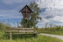 Cruz del borde del camino y banco de madera en el bosque bávaro en el ¼ b de Grà con Grafenau Imagen de archivo