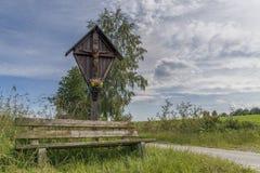 Cruz del borde del camino y banco de madera en el bosque bávaro en el ¼ b de Grà por Grafenau Imágenes de archivo libres de regalías