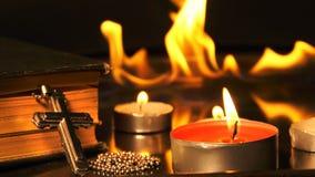 Cruz del cristianismo y velas y fuego detrás almacen de video