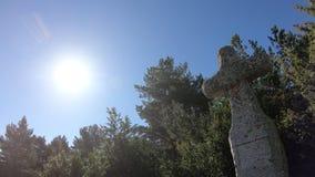 Cruz del granito y sol brillante en los Pirineos franceses, Aude en meridional de Francia