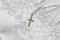 Cruz del oro con el primer vestido de la comunión Fotos de archivo libres de regalías
