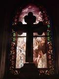 Cruz delante de un vidrio manchado imagenes de archivo
